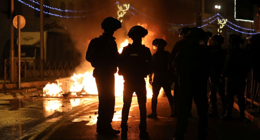 Israeli police officers stand next to a burning barricade during clashes, as the Muslim holy fasting month of Ramadan continues, in Jerusalem, April 22, 2021