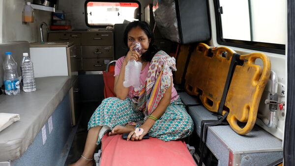 A patient with respiratory problems wears an oxygen mask as she waits inside an ambulance which is queuing to enter a COVID-19 hospital, as the coronavirus disease pandemic surges, Ahmedabad, India, 14 April 2021. - Sputnik International