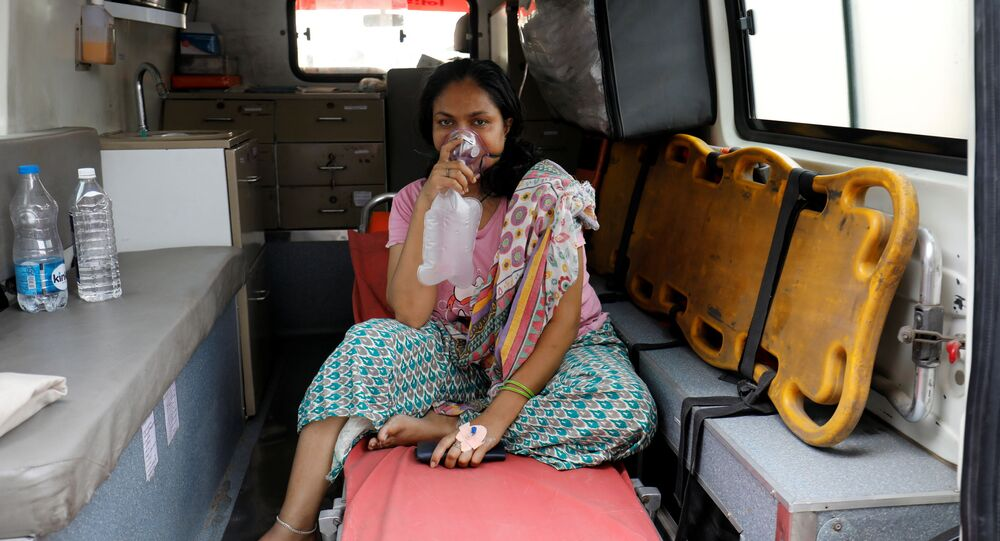 A patient with respiratory problems wears an oxygen mask as she waits inside an ambulance which is queuing to enter a COVID-19 hospital, as the coronavirus disease pandemic surges, Ahmedabad, India, 14 April 2021.