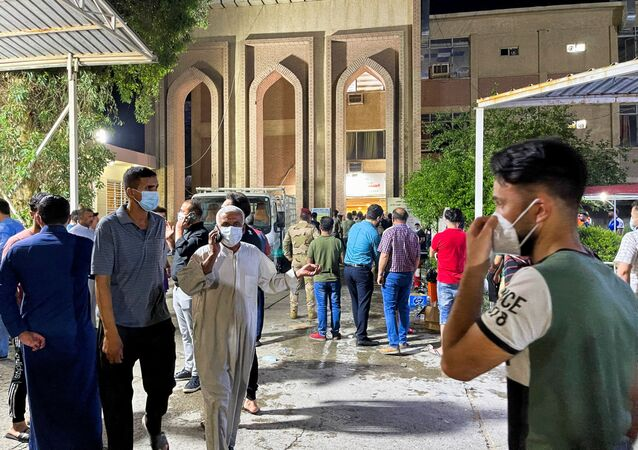 People gather inside Ibn Khatib hospital after a fire caused by an oxygen tank explosion in Baghdad, Iraq, April 25, 2021