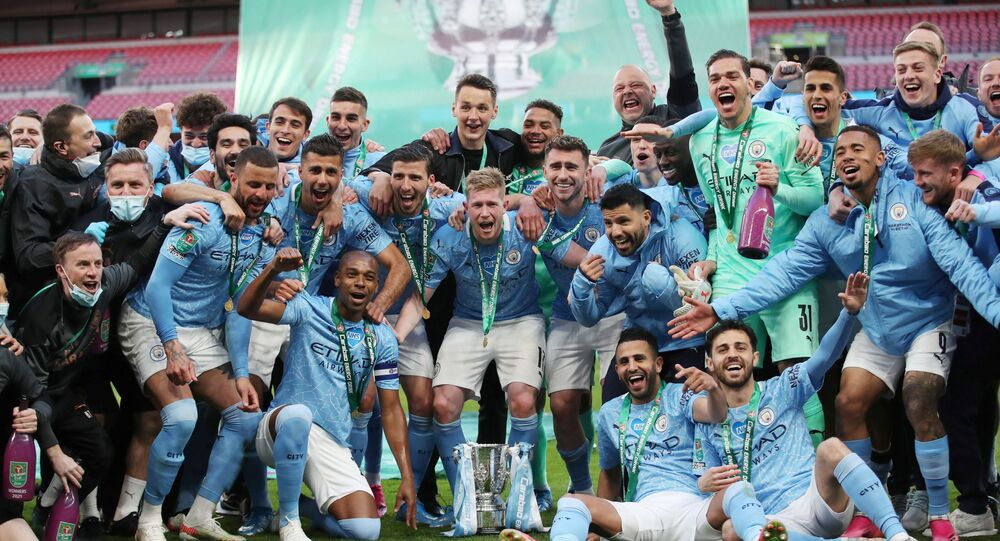 Manchester City players pose with the trophy as they celebrate after winning the Carabao Cup