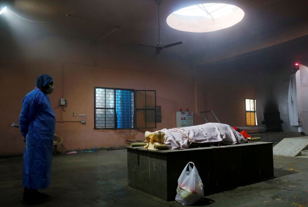 A family member wearing personal protective equipment (PPE) stands next to the body of a woman, who died from the coronavirus disease (COVID-19), before her cremation in New Delhi, India, 24 April 2021.