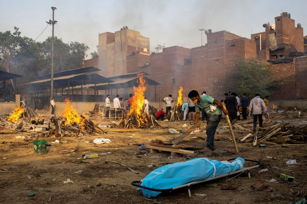A man prepares a funeral pyre to cremate the body of a person who died from the coronavirus disease (COVID-19) at a crematorium ground in New Delhi, India, 22 April 2021.