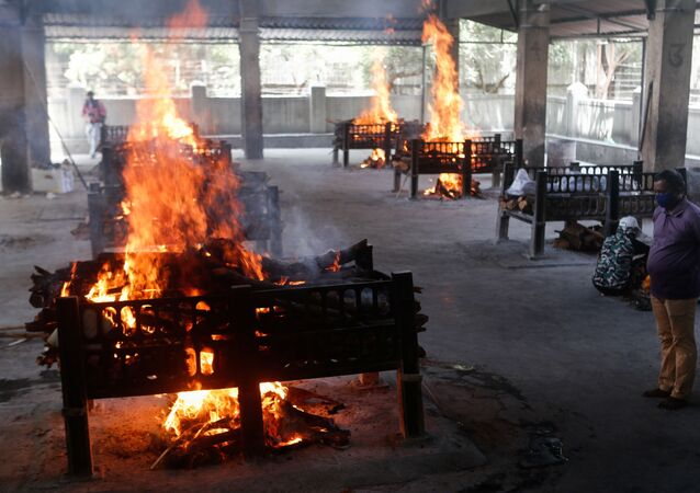 A relative of a coronavirus disease (COVID-19) patient who passed away after a hospital caught fire looks on as funeral pyres burn inside a crematorium in Virar, on the outskirts of Mumbai, India, 23 April 2021