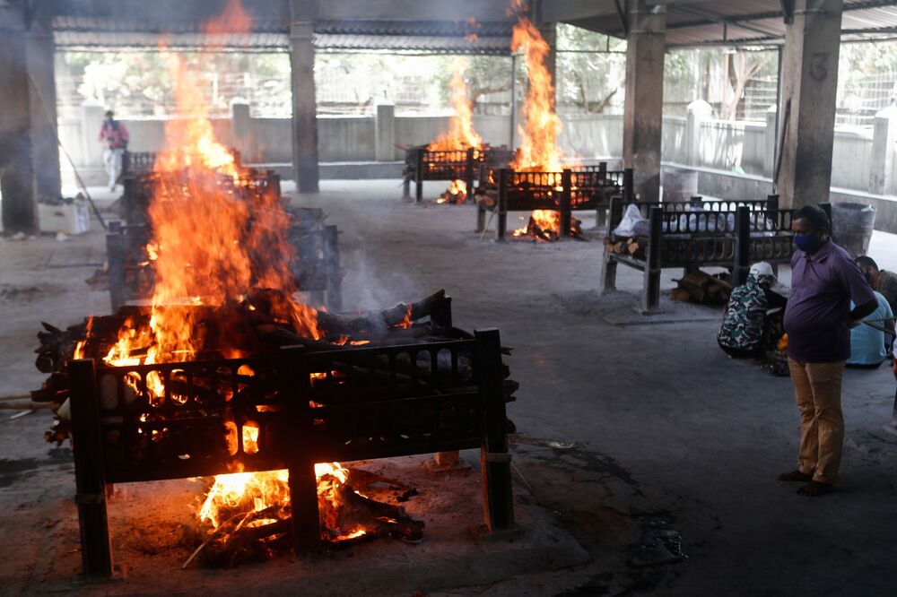 A relation of a coronavirus disease (COVID-19) patient who died after a hospital caught fire looks on as funeral pyres burn inside a crematorium in Virar, on the outskirts of Mumbai, India, 23 April 2021.