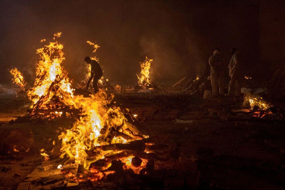 People cremate the bodies of victims of the coronavirus disease (COVID-19) at a crematorium ground in New Delhi, India, 24 April 2021.