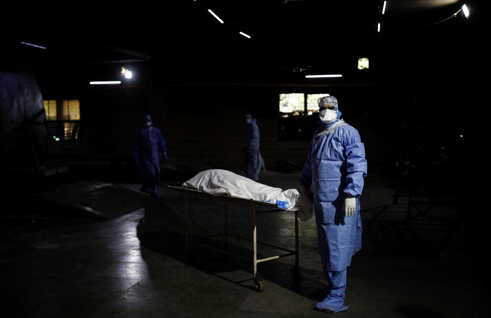 A health worker wearing personal protective equipment (PPE) stands next to the body of a man, who died from the coronavirus disease (COVID-19), at a crematorium in New Delhi, India 21 April 2021.