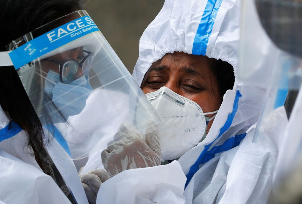 Relations wearing personal protective equipment (PPE) mourn a man who died from the coronavirus disease (COVID-19), during his funeral at a crematorium in New Delhi, India, 21 April 2021.