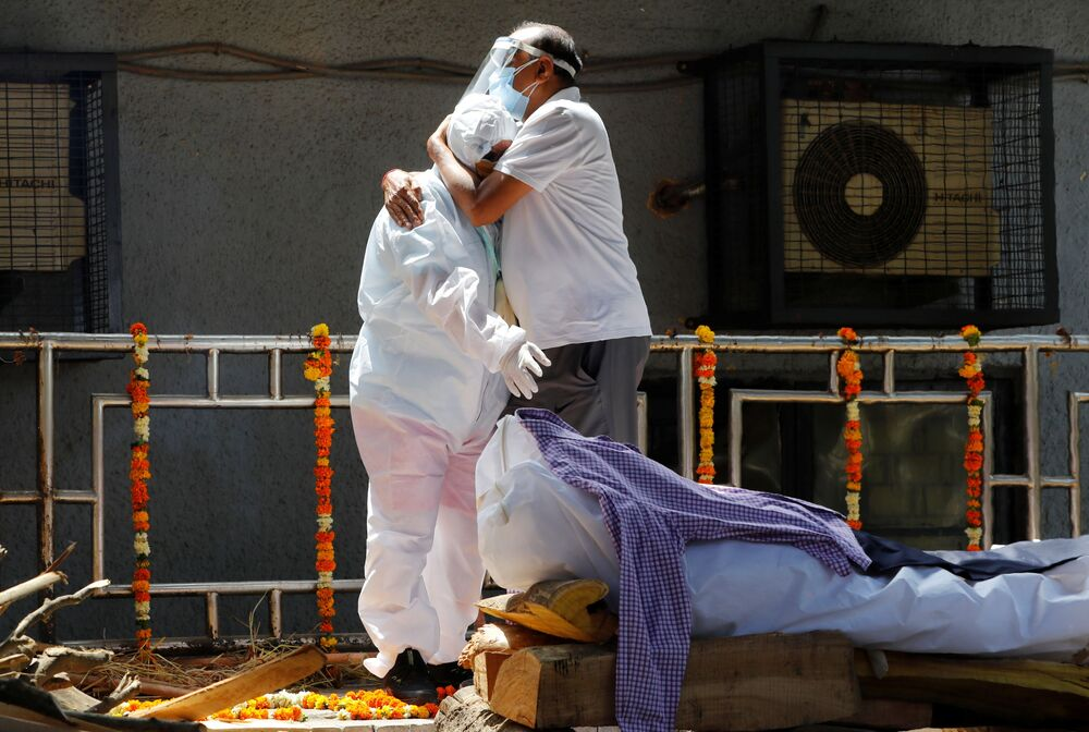 Relations wearing personal protective equipment (PPE) mourn a man who died from the coronavirus disease (COVID-19) next to his funeral pyre at a crematorium in New Delhi, India, 21 April 2021.