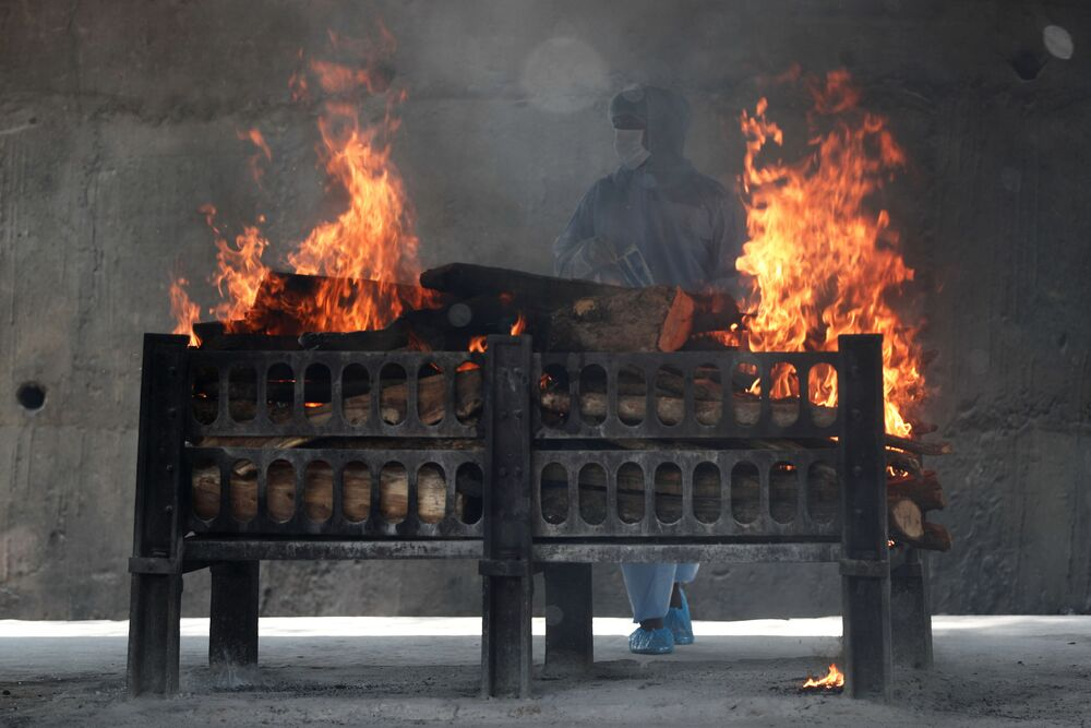 A frontline worker looks on as the funeral pyre of a man who died from the coronavirus disease  (COVID-19) burns at a crematorium on the outskirts of Mumbai, India, 15 April 2021.