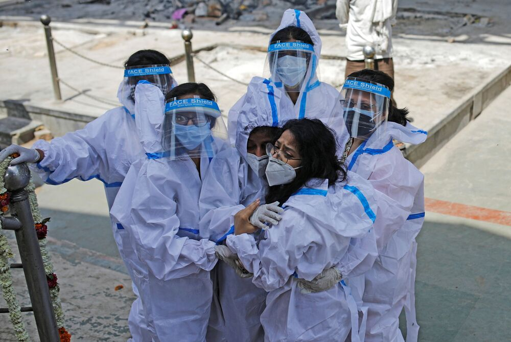Relations wearing personal protective equipment (PPE) mourn a man who died from the coronavirus disease (COVID-19) at a crematorium in New Delhi, India, 21 April 2021.