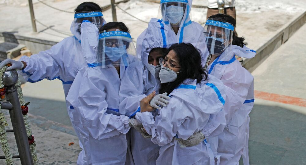 Relatives wearing personal protective equipment (PPE) mourn a man, who died from coronavirus disease (COVID-19), at a crematorium in New Delhi, India April 21, 2021.