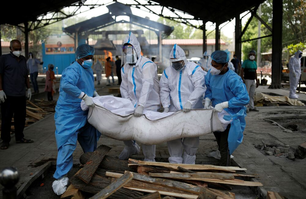 Health workers and relations wearing personal protective equipment (PPE) carry the body of a man who died from coronavirus disease (COVID-19), at a crematorium in New Delhi, India, 21 April 2021.