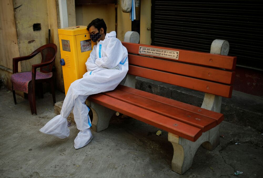 An exhausted health worker wearing personal protective equipment (PPE) rests at a crematorium in New Delhi, India, 21 April 2021.