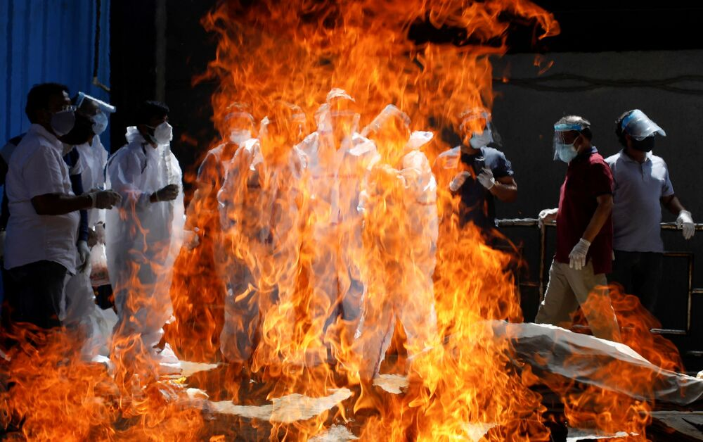 Relations wearing personal protective equipment (PPE) attend the funeral of a man who died from the coronavirus disease (COVID-19), at a crematorium in New Delhi, India, 21 April 2021.