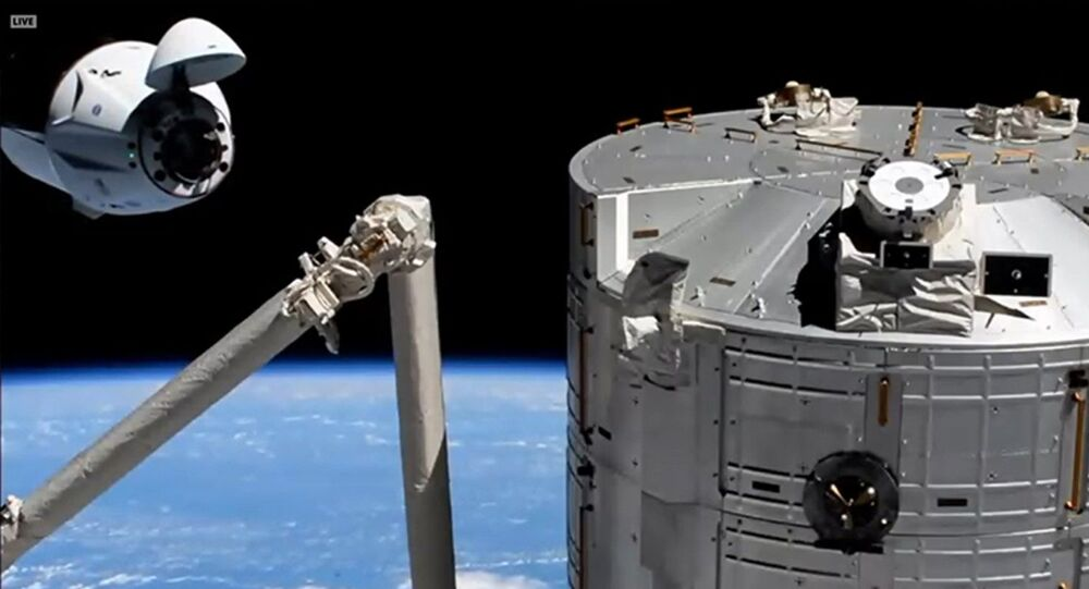 The SpaceX Crew Dragon approaches its space station docking port with the Kibo laboratory module in the foreground.