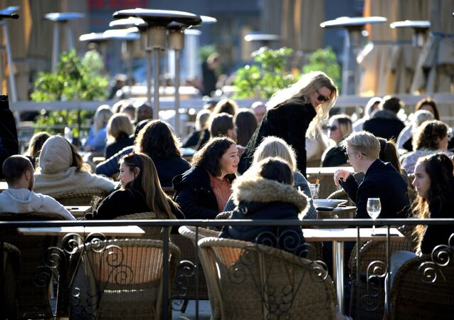 FILE PHOTO: People enjoy the sun at an outdoor restaurant, despite the continuing spread of coronavirus disease (COVID-19), in Stockholm, Sweden March 26, 2020.
