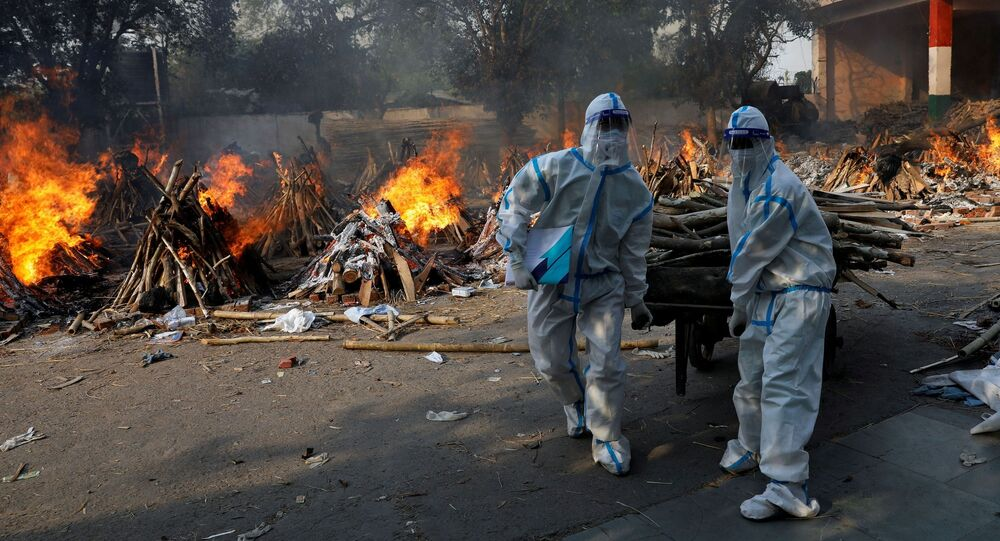 Health workers wearing personal protective equipment (PPE) carry wood to prepare a funeral pyre for a coronavirus disease (COVID-19) victim during a mass cremation at a crematorium in New Delhi, India, April 26, 2021