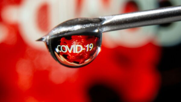 FILE PHOTO: The word COVID-19 is reflected in a drop on a syringe needle in this illustration taken November 9, 2020. - Sputnik International