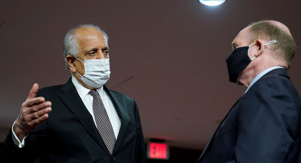 Zalmay Khalilzad, special envoy for Afghanistan Reconciliation, talks with U.S. Senator Chris Coons (D-DE), before the start of a Senate Foreign Relations Committee hearing on Capitol Hill in Washington, U.S., April 27, 2021.