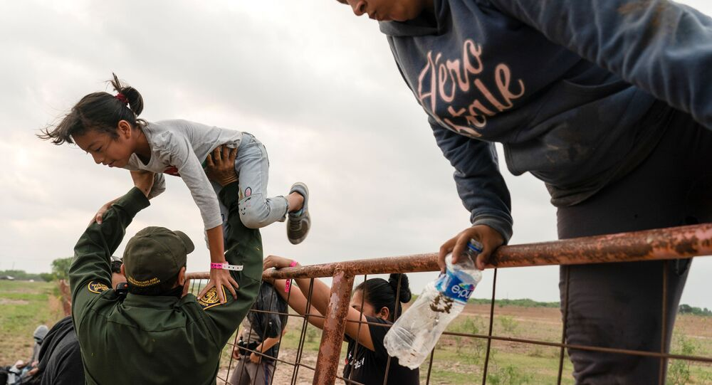 Central American migrants climb over a fence as they are detained by U.S. Border Patrol agents after crossing the Rio Grande river into the United States from Mexico in La Joya, Texas, U.S.,  April 27, 2021.