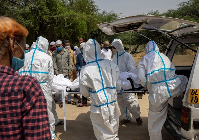 Healthcare workers and relatives carry the body of a person, who died from the coronavirus disease (COVID-19), for his burial at a graveyard in New Delhi, India, April 28, 2021.