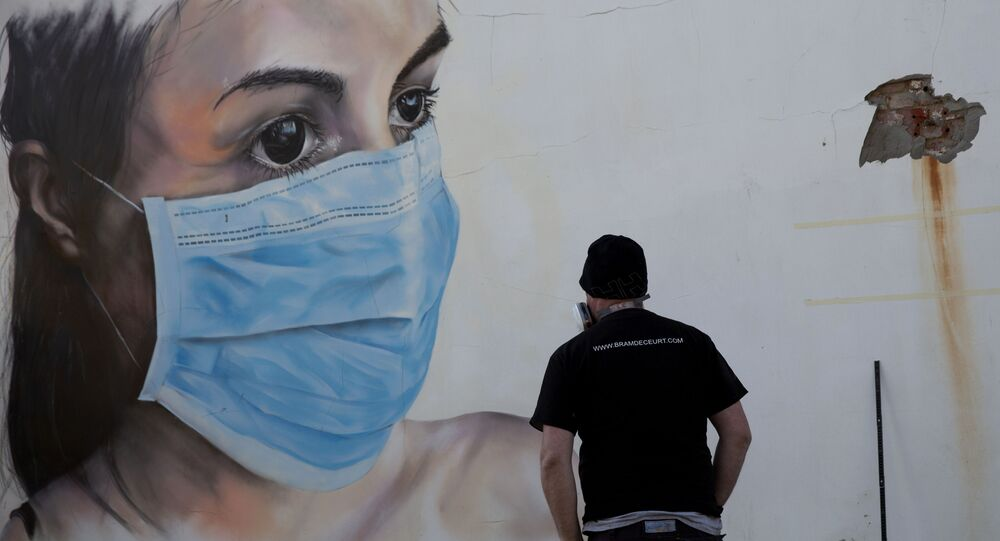 Graffiti artist Bram De Ceurt takes a step back as he works on a street graffiti piece of a nurse with a mouth mask to protect against coronavirus in Antwerp, Belgium, Thursday, March 26, 2020