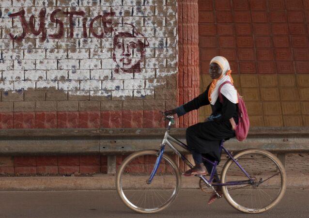 A girl rides a bicycle past graffiti reading Justice with a picture of slain ex-President Thomas Sankara in Ouagadougou, Burkina Faso, December 4, 2015.