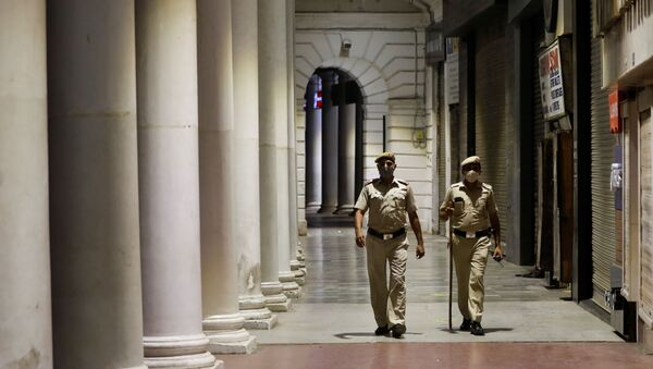 Police officers patrol in front of closed shops at a market area during a curfew to limit the spread of the coronavirus disease (COVID-19), in New Delhi, India, April 6, 2021. - Sputnik International