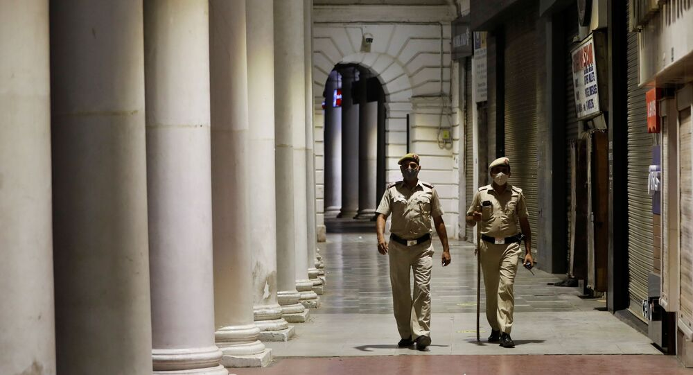 Police officers patrol in front of closed shops at a market area during a curfew to limit the spread of the coronavirus disease (COVID-19), in New Delhi, India, 6 April 2021.
