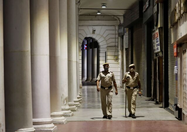 Police officers patrol in front of closed shops at a market area during a curfew to limit the spread of the coronavirus disease (COVID-19), in New Delhi, India, April 6, 2021.
