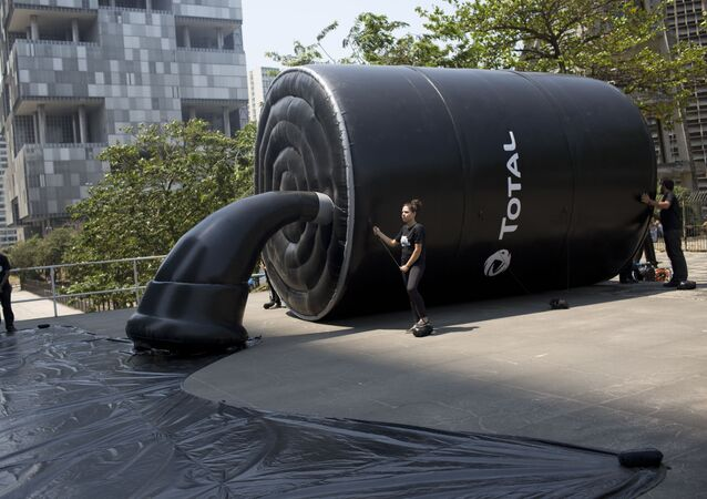 Greenpeace activists stand by an inflatable structure mimicking a barrel spilling oil as they protest outside France's Total oil company's headquarters in Rio de Janeiro, Brazil, Thursday, Sept. 28, 2017