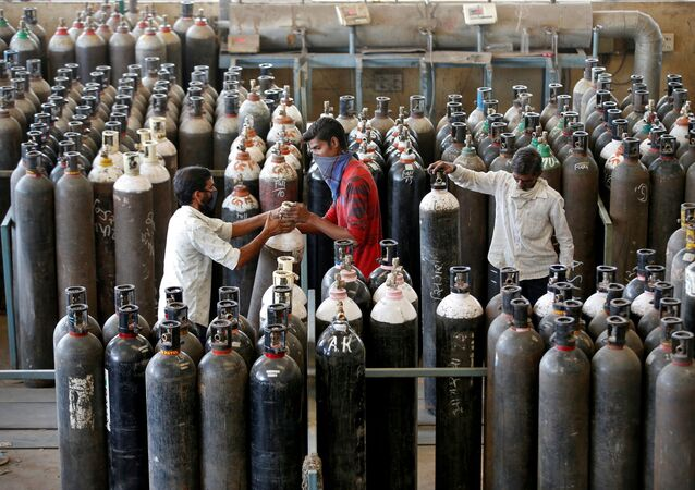 People carry oxygen cylinders after refilling them in a factory, amidst the spread of the coronavirus disease (COVID-19) in Ahmedabad, India, April 25, 2021