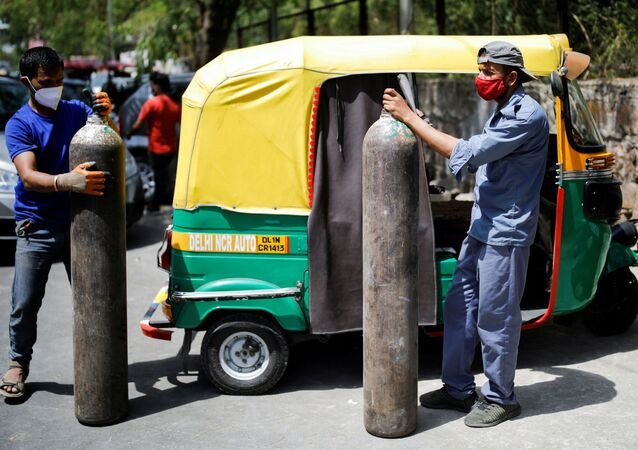 Rickshaw drivers hold oxygen cylinders outside a private refilling station, amid the coronavirus disease (COVID-19) outbreak, in New Delhi, India, April 19, 2021