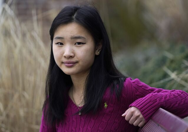 High school student Grace Hu, 16, of Sharon, Mass., stands for a photograph near Sharon High School, Sunday, April 11, 2021, in Sharon. Hu, who plans to to go back to in-person classes in April, helped organize a rally in Boston in early April against anti-Asian hate, but said she's not concerned about facing vitriol when her school reopens fully.