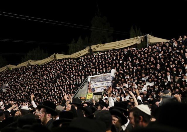 Jewish worshippers sing and dance as they stand on tribunes at the Lag B'Omer event in Mount Meron, northern Israel, April 29, 2021.