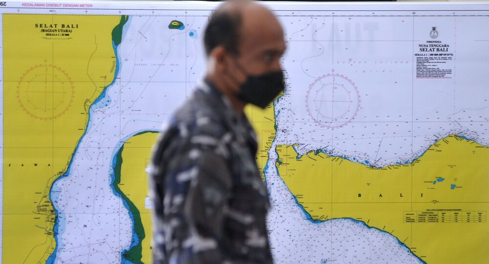 An Indonesian Navy serviceman walks past a map of the searching area for the submarine KRI Nanggala-402, which lost contact while drilling torpedo shooting on Wednesday, at I Gusti Ngurah Rai airport in Bali, Indonesia, 23 April 2021 in this photo taken by Antara Foto