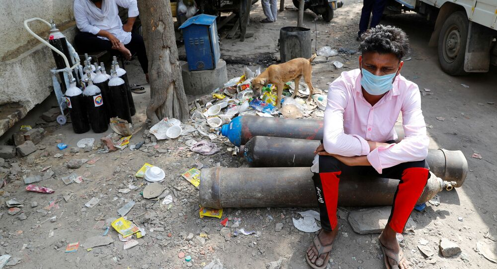 Sumit Kumar, 28, sits on an oxygen cylinder as he waits outside a factory to get it refilled, as the number of infections from the coronavirus disease (COVID-19) soars in New Delhi, India.