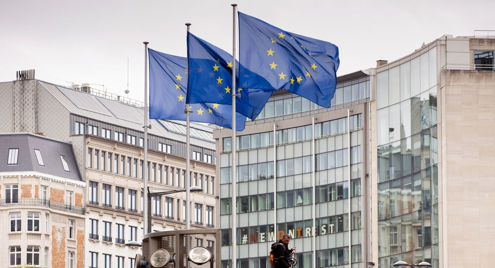 European Union flags flap in the wind as two gardeners work on the outside of EU headquarters in Brussels, Wednesday, Sept. 11, 2019.