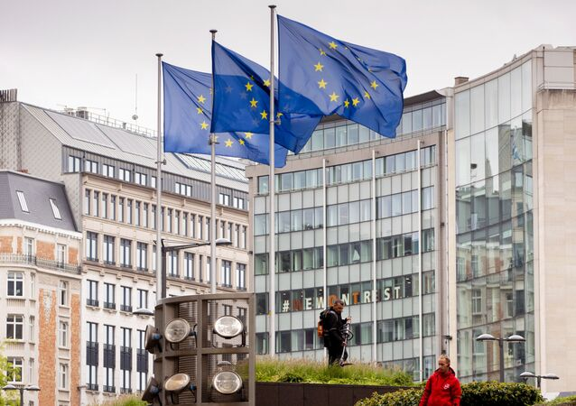 European Union flags flap in the wind as two gardeners work on the outside of EU headquarters in Brussels, Wednesday, 11 September 2019.