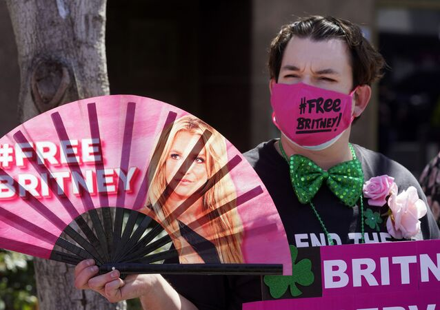 Britney Spears supporter Dustin Strand of Phoenix holds a hand fan outside a court hearing concerning the pop singer's conservatorship at the Stanley Mosk Courthouse, Wednesday, March 17, 2021, in Los Angeles