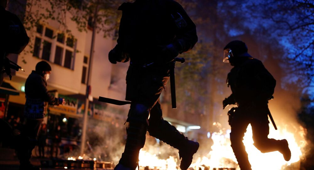 Police officers run past a fire during a left-wing May Day demonstration, as the spread of the coronavirus disease (COVID-19) continues in Berlin, Germany, May 1, 2021.
