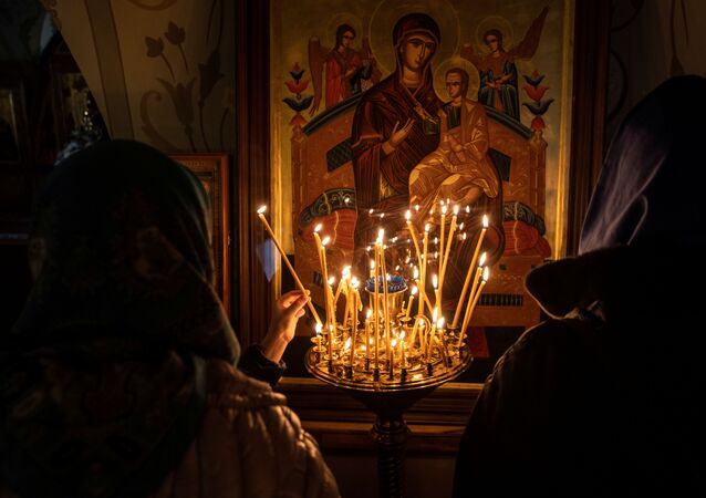 Women light candles in front of an icon on the eve of Orthodox Easter in the Joseph-Volokolamsk monastery in Moscow region, Russia May 1, 2021.