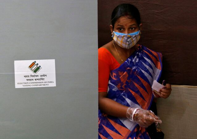 A woman wearing a protective face mask leaves after casting her vote at a polling station during the seventh phase of West Bengal state election, amidst the spread of the coronavirus disease (COVID-19), in Kolkata, India