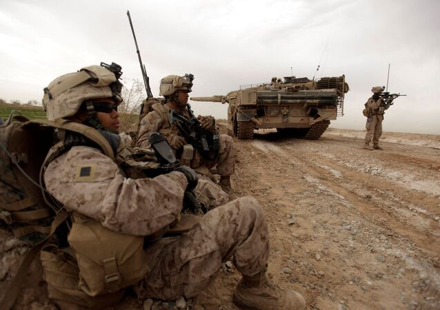 In this file photo taken on February 21, 2010, US marines with 1/3 marine Charlie Company patrol past a Danish army Leopard 2A5EK tank as they clear Improvised Explosive Device (IED)s from a main route in Trikh Nawar on the North Eastern outskirts of Marjah in Afghanistan