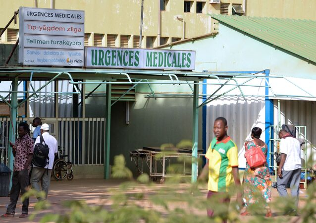 People stand outside the entrance of the emergency services at the Yalgado hospital in Ouagadougou on November 22, 2016, as doctors and health workers started a strike launched by the National union of human and animal health workers, to ask for salary hikes and increased allowances.