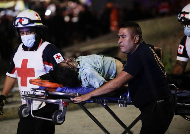 Rescuers wheel an injured person on a stretcher a site where an overpass for a metro partially collapsed with train cars on it at Olivos station in Mexico City, Mexico May 3, 2021.