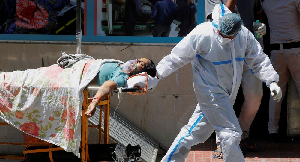 FILE PHOTO: A health worker wearing personal protective equipment (PPE) carries a patient suffering from the coronavirus disease (COVID-19) outside the casualty ward at Guru Teg Bahadur hospital, in New Delhi, India, April 24, 2021.