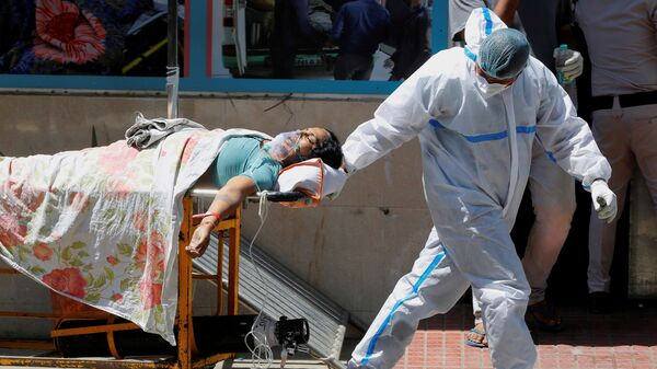 FILE PHOTO: A health worker wearing personal protective equipment (PPE) carries a patient suffering from the coronavirus disease (COVID-19) outside the casualty ward at Guru Teg Bahadur hospital, in New Delhi, India on 24 April 2021. - Sputnik International