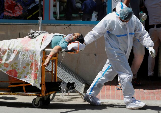 FILE PHOTO: A health worker wearing personal protective equipment (PPE) carries a patient suffering from the coronavirus disease (COVID-19) outside the casualty ward at Guru Teg Bahadur hospital, in New Delhi, India, 24 April 2021.